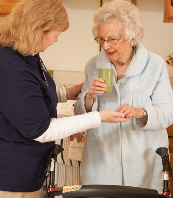 Certified Nursing Assistant helps resident with meds in her apartment at Laurel View Village, Davidsville, PA
