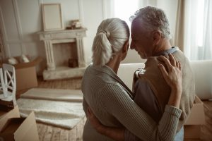Elderly White Couple Moving Out of Home and Hugging and Looking at Their Living Room