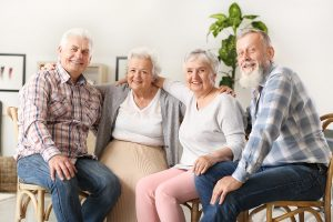 Two Elderly Couples Sitting and Smiling Together